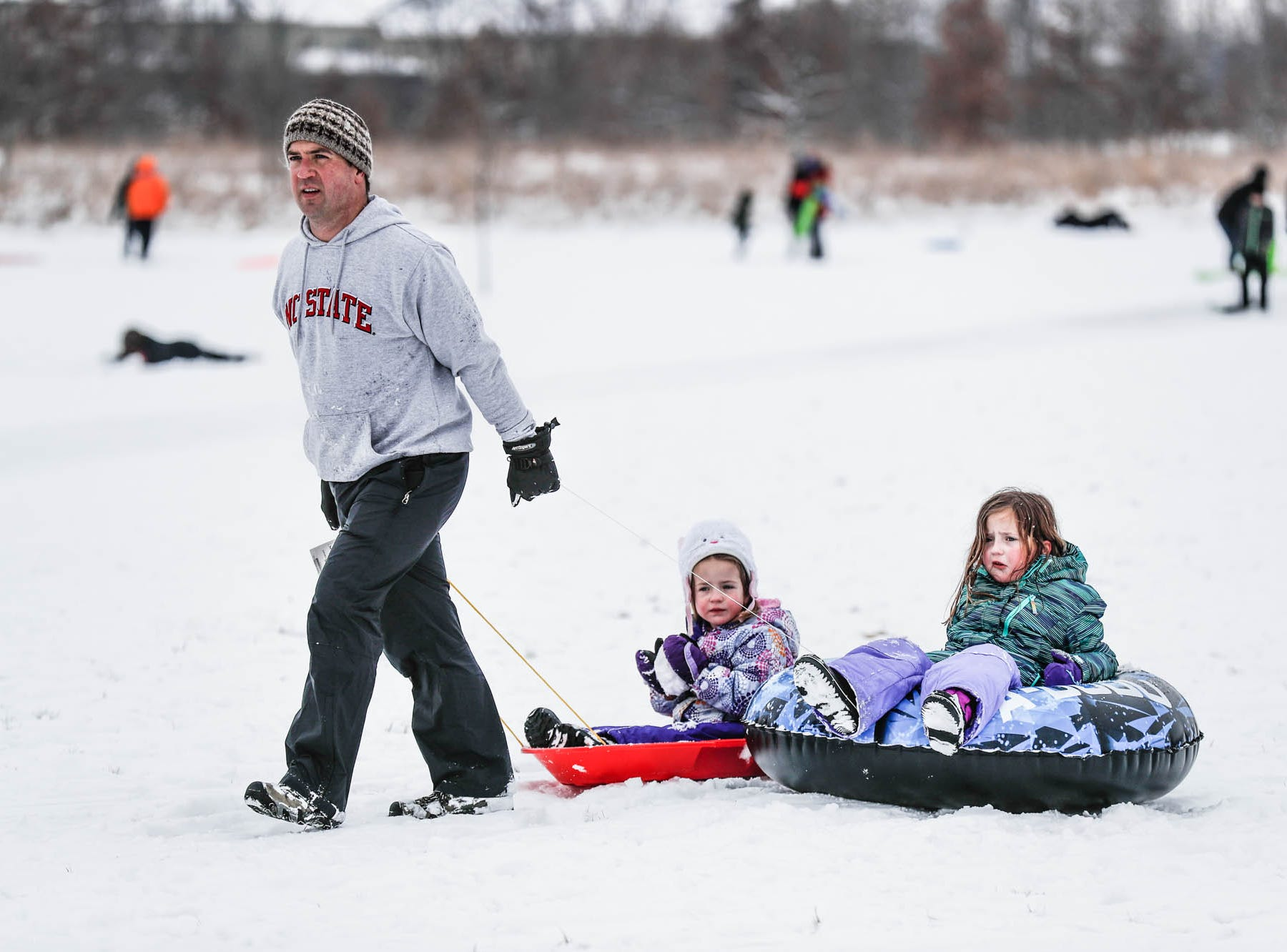 Paul Weber pulls his daughters Caitlyn, left, and Olivia to the car after an afternoon of sledding at West Park in Carmel Ind. on Sunday, Jan. 13, 2019.