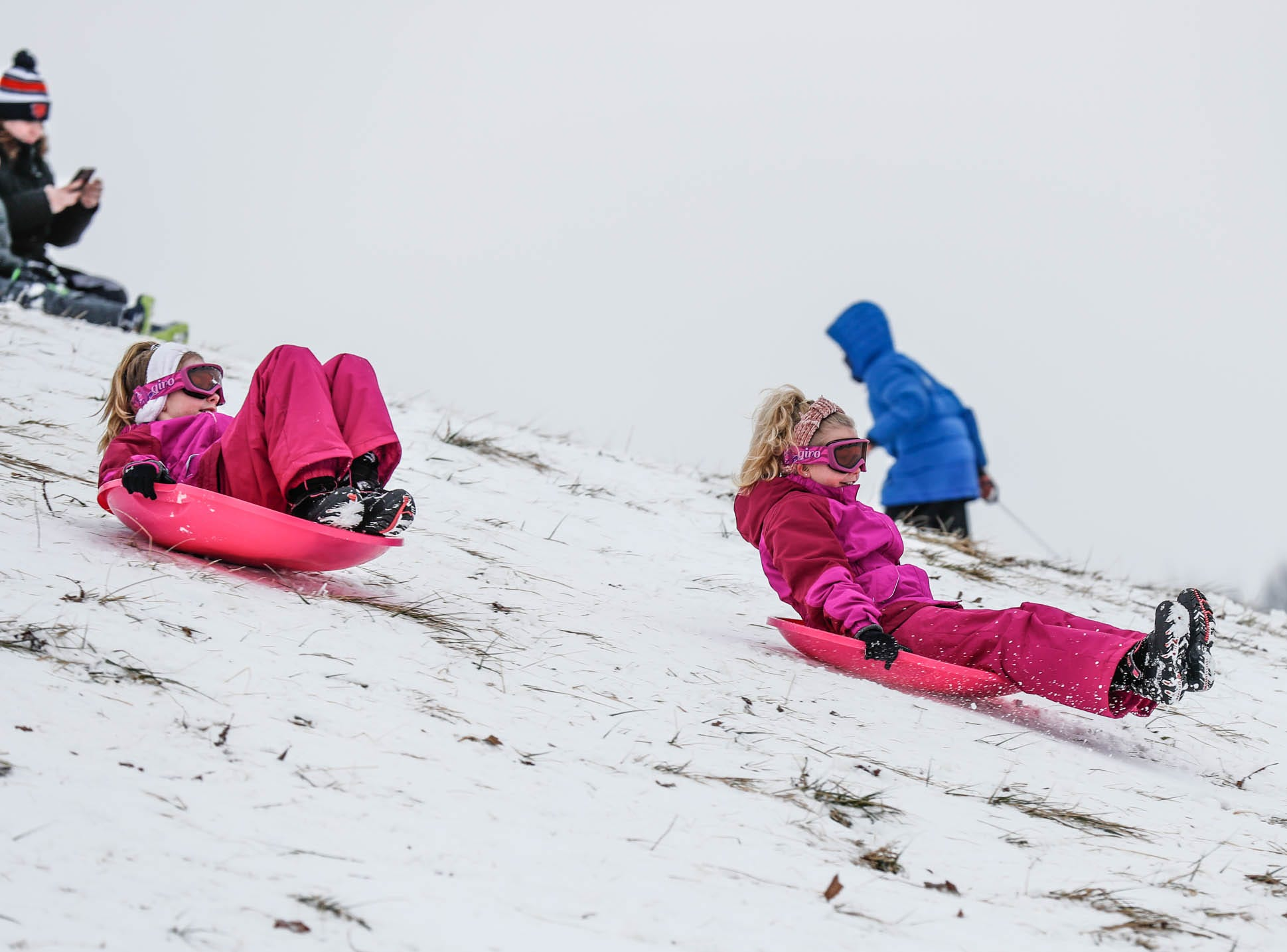 Avery, left, and Macey Lerette zoom down the sledding hill at West Park in Carmel Ind. on Sunday, Jan. 13, 2019.