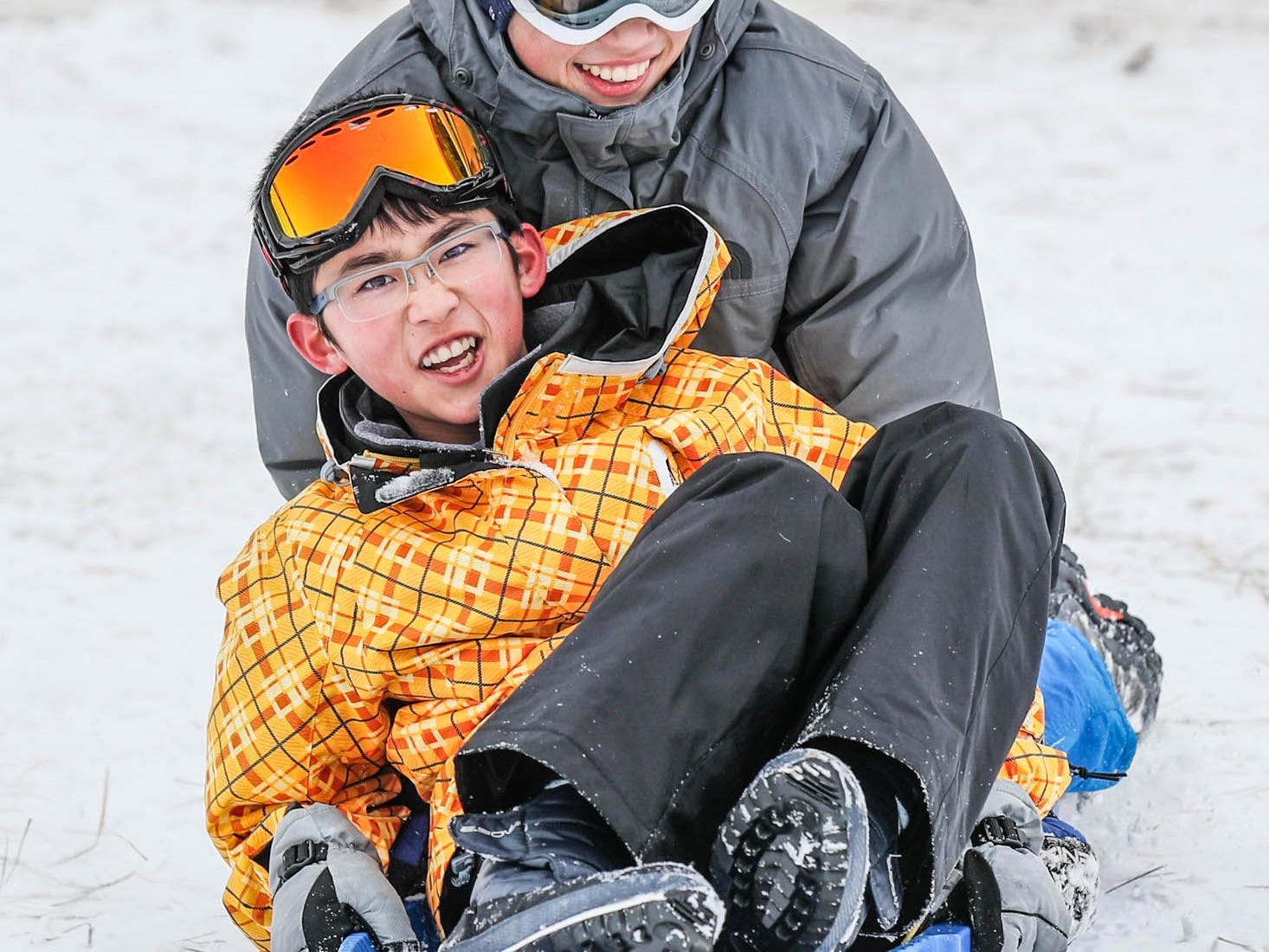 Brothers Yoshito, front, and Yuto Endo, rear, zoom down the sledding hill at West Park in Carmel Ind. on Sunday, Jan. 13, 2019.