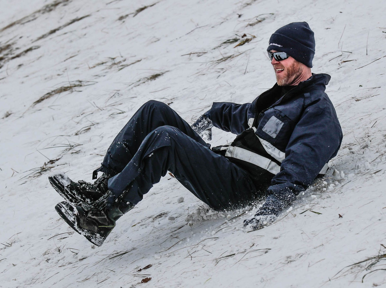 An unidentified man slides down the hill at West Park in Carmel Ind. on Sunday, Jan. 13, 2019.