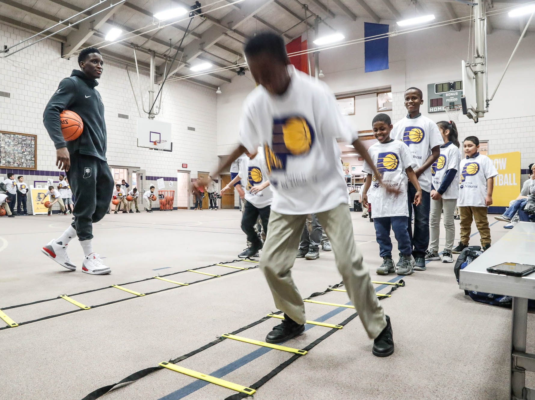 Indiana Pacers guard Victor Oladipo watches children run warm up drills after surprising them during a Jr. Pacers Clinic at Concord Neighborhood Center, on Monday, Jan. 14, 2019.