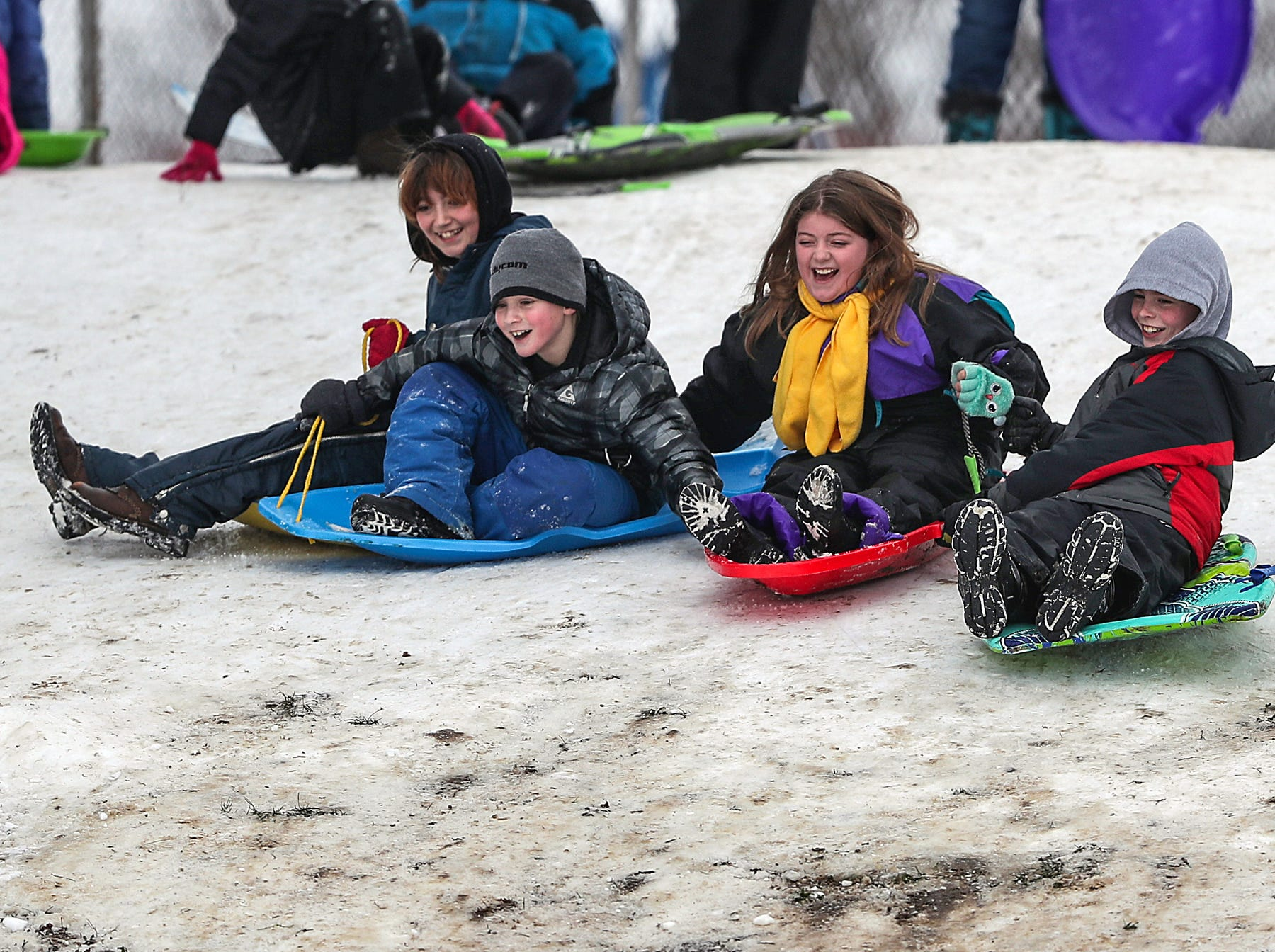 A group of children sled down the hill at Ellenberger Park in Indianapolis, Sunday, Jan. 13, 2019.