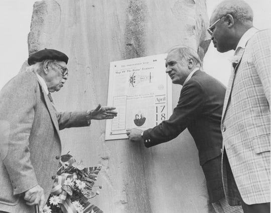 """Indianapolis artist Elmer Taflinger (left), who was the guiding force behind the renovation of Holliday Park, discusses """"The Ruins"""" plaque with Mayor William Hudnut and Parks director Ray Crowe (right). The three men inspect one of The Indianapolis Star's memorial plaques, which contain stories about the history and meaning of the art."""