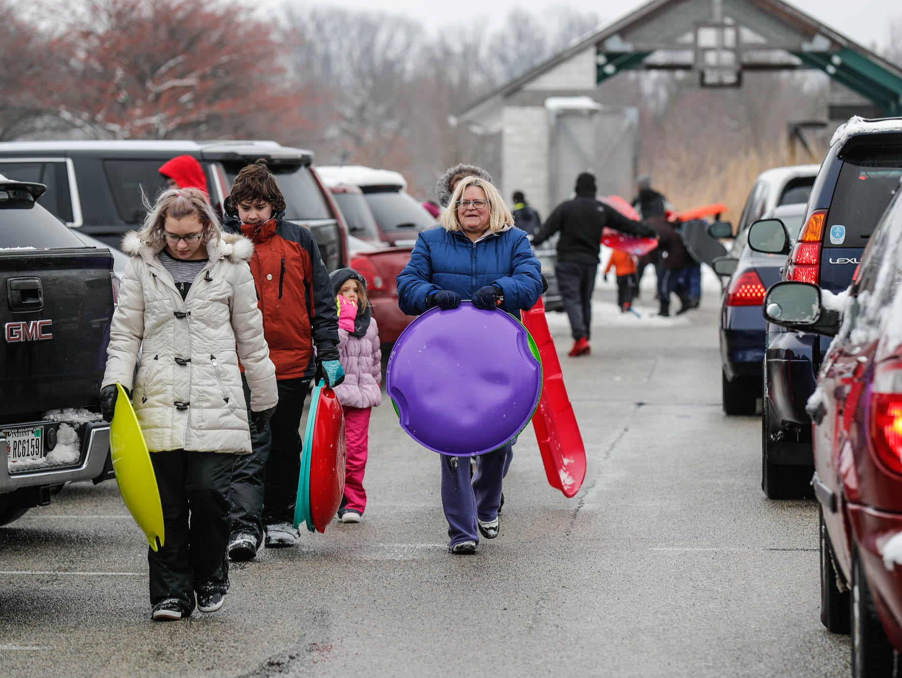 Visitors line up in cars to pick up and drop off near the sledding hill at West Park in Carmel Ind. on Sunday, Jan. 13, 2019.
