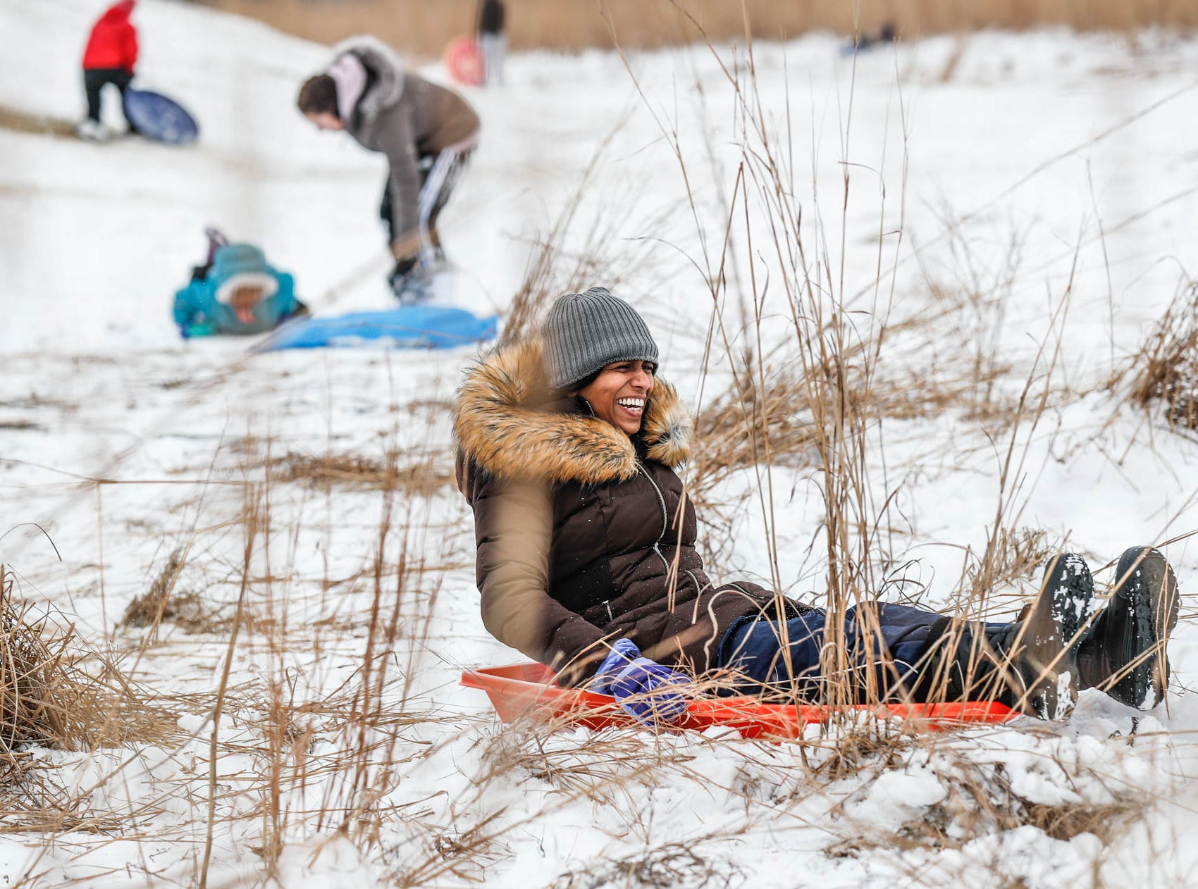 Fathima Mohammed zooms down the sledding hill and in to the tall grass at West Park in Carmel Ind. on Sunday, Jan. 13, 2019.