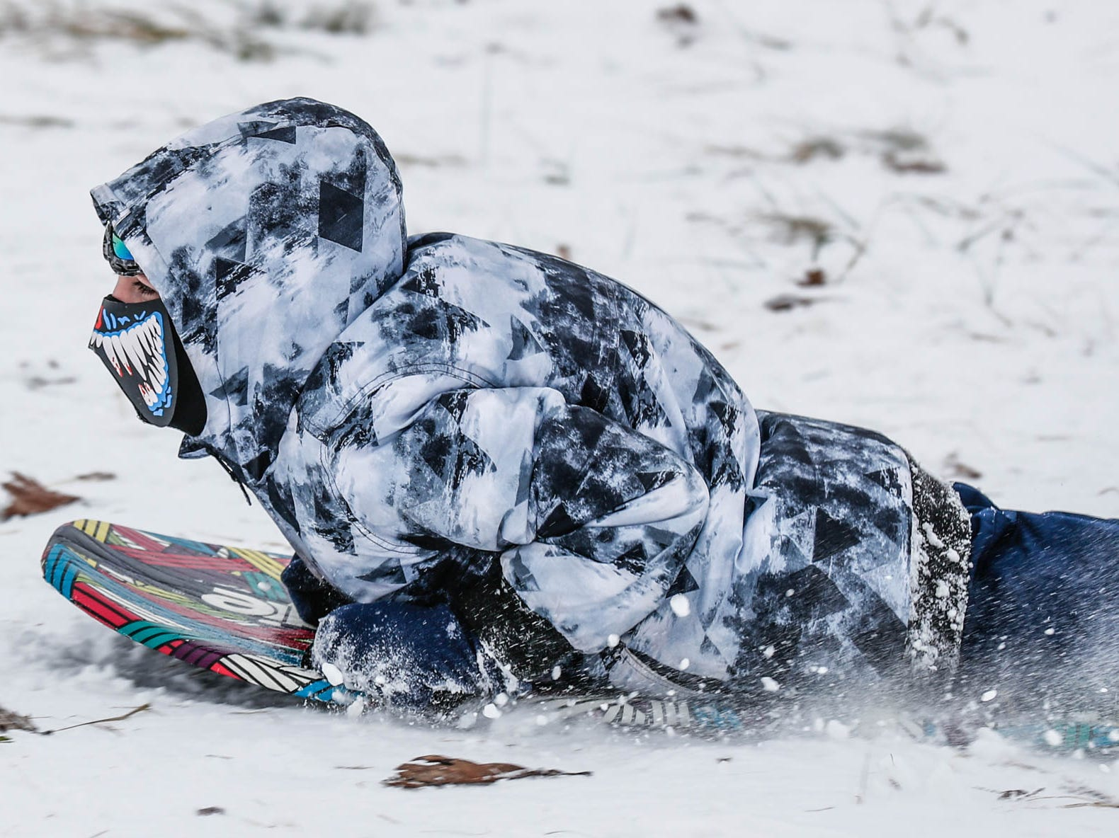 A unidentified child zooms down the sledding hill at West Park in Carmel Ind. on Sunday, Jan. 13, 2019.