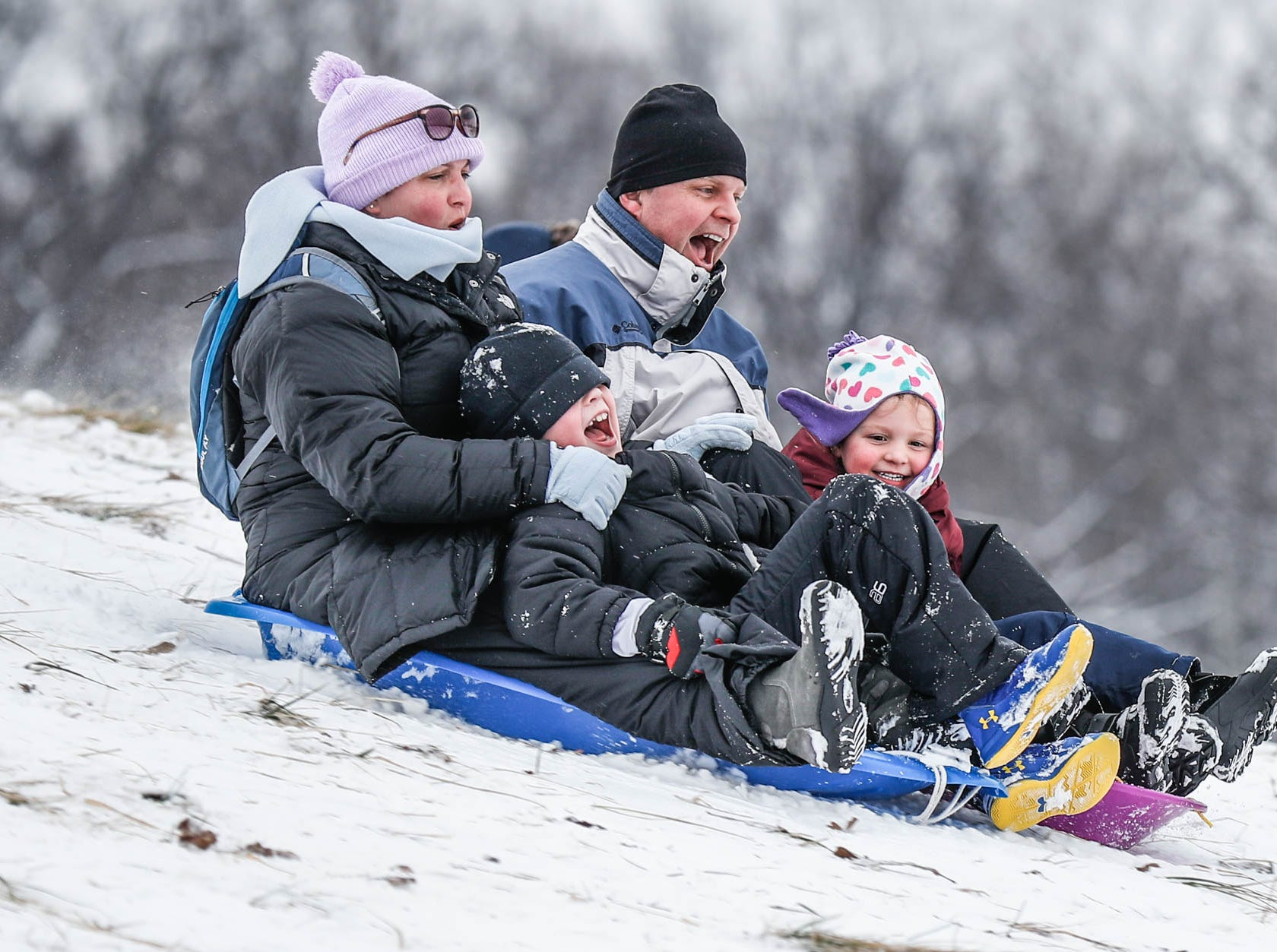 Sheri and Paul Wood zoom down the sledding hill at West Park in Carmel Ind. with their children Ben, left, and Izzy, on Sunday, Jan. 13, 2019.