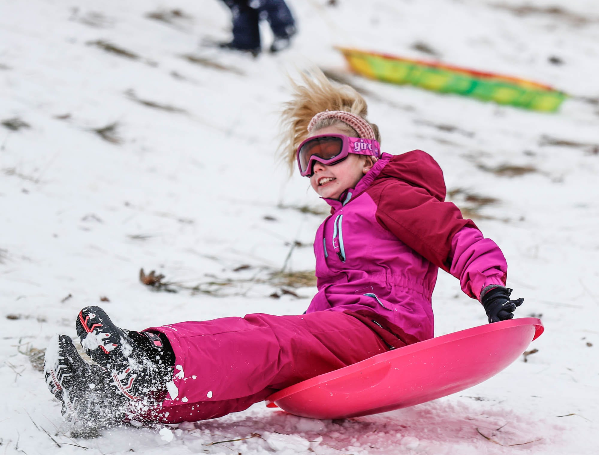 Macey Lerette zooms down the sledding hill at West Park in Carmel Ind. on Sunday, Jan. 13, 2019.