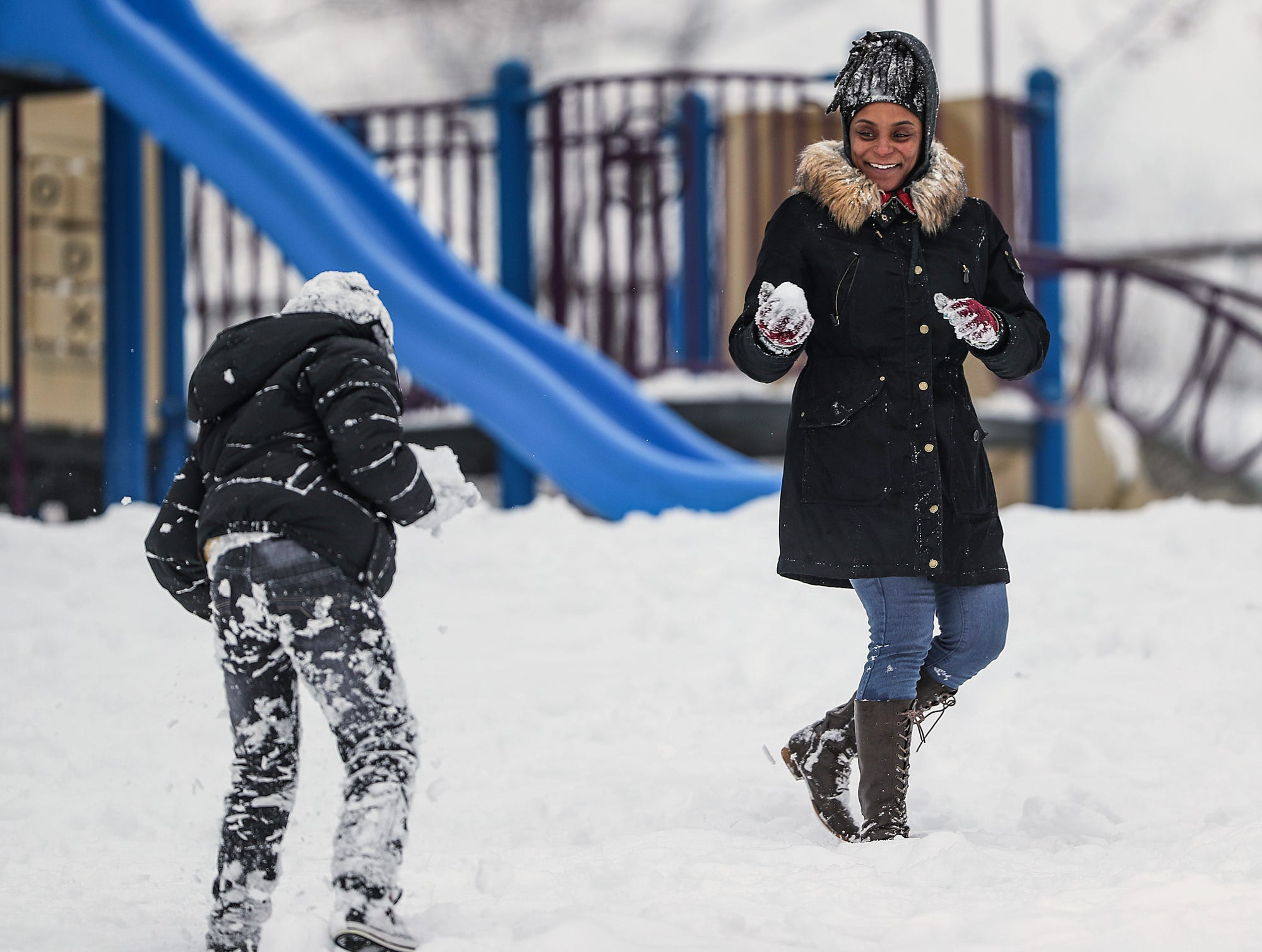 From left, Julian Linton, 8, and his mother Jilliane Linton have a snowball fight at Ellenberger Park in Indianapolis, Sunday, Jan. 13, 2019 Saturday's storm left Indianapolis blanketed in more than 7 inches of snow.