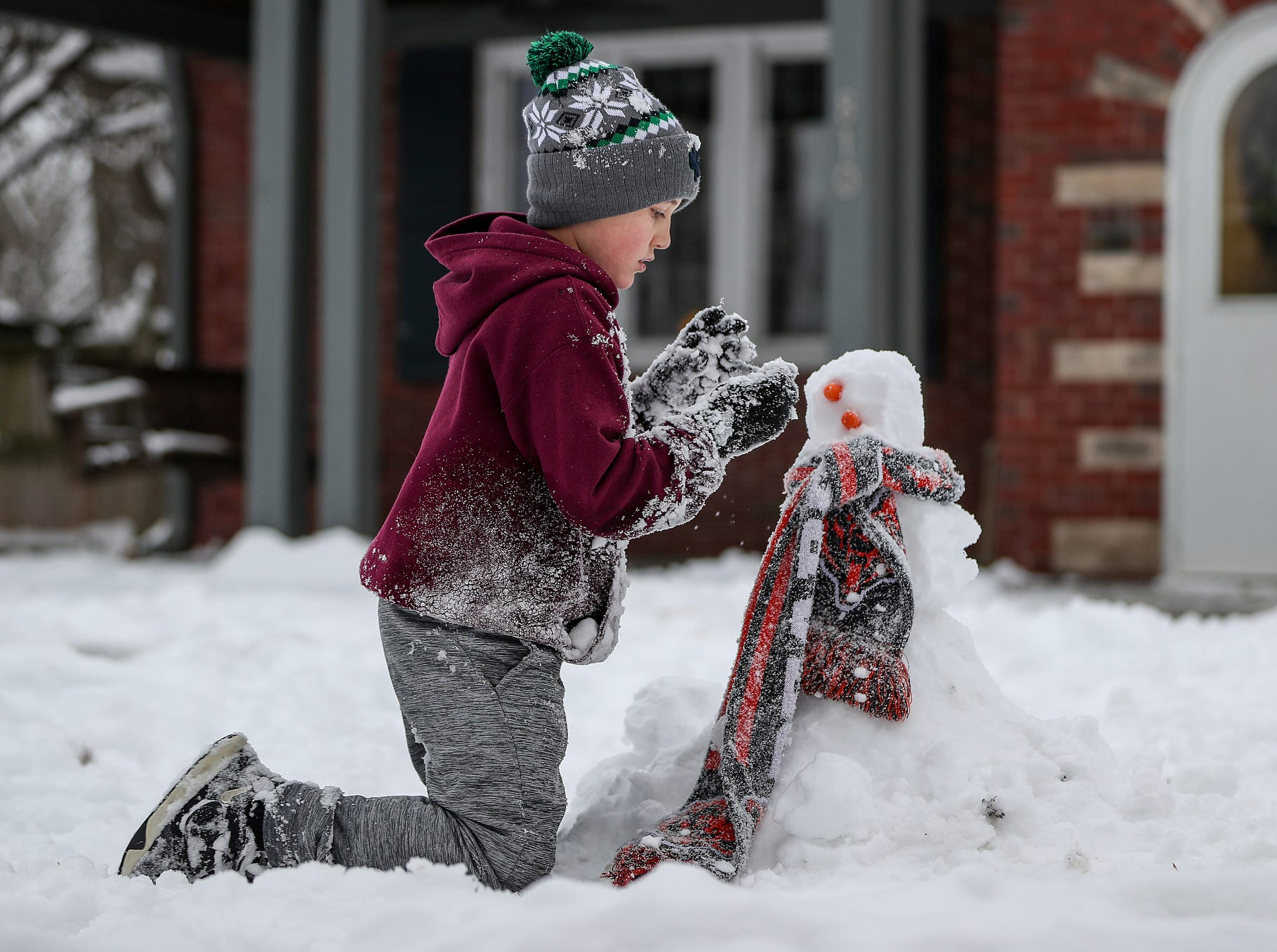 Evan Bollenbacher, 8, builds a snowman in the front yard of his eastside home in Indianapolis, Sunday, Jan. 13, 2019. Saturday's storm left Indianapolis blanketed in more than 7 inches of snow.