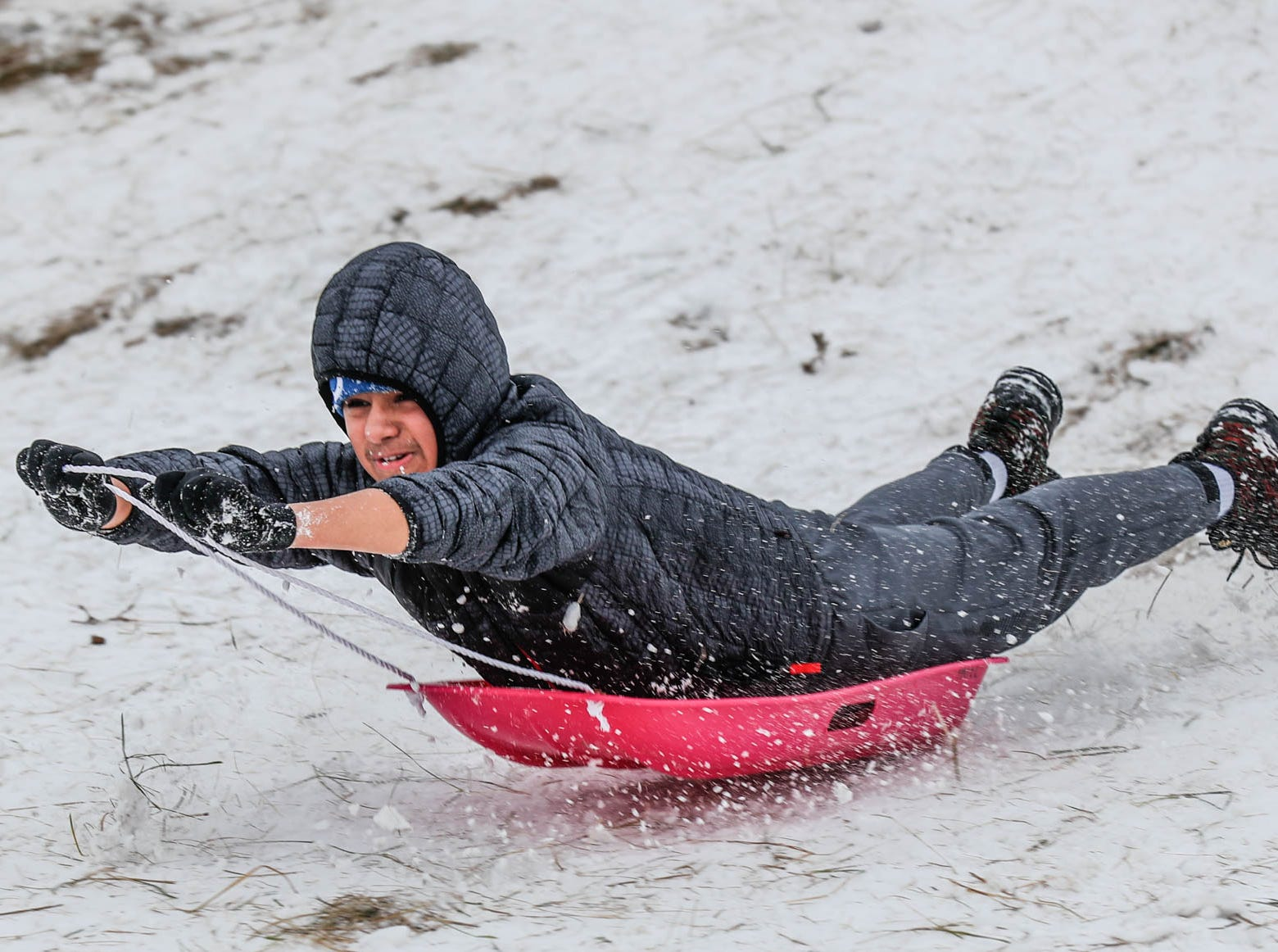 Armaan Patel hits a bump while riding down the sledding hill at West Park in Carmel Ind. on Sunday, Jan. 13, 2019.