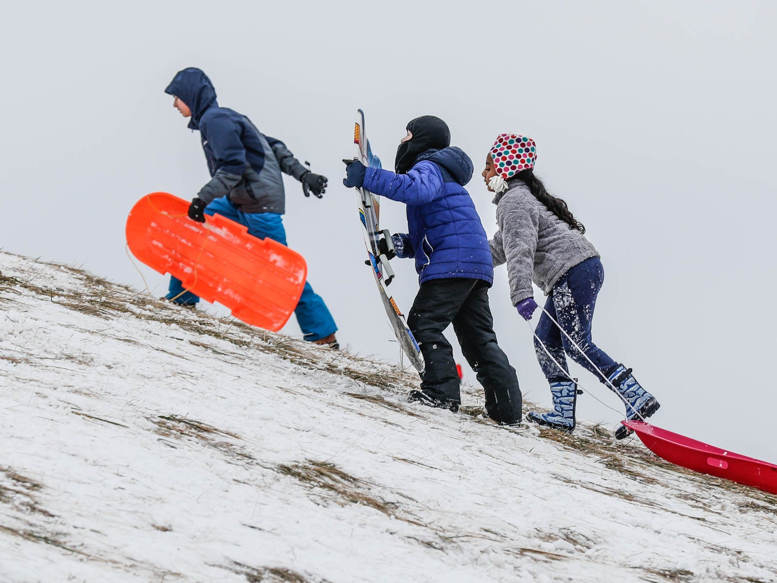 Unidentified children make their way up the sledding hill at West Park in Carmel Ind. on Sunday, Jan. 13, 2019.