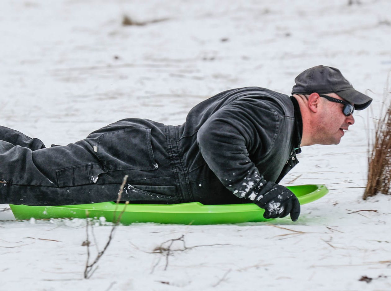 An unidentified man sleds down the hill at West Park in Carmel Ind. on Sunday, Jan. 13, 2019.