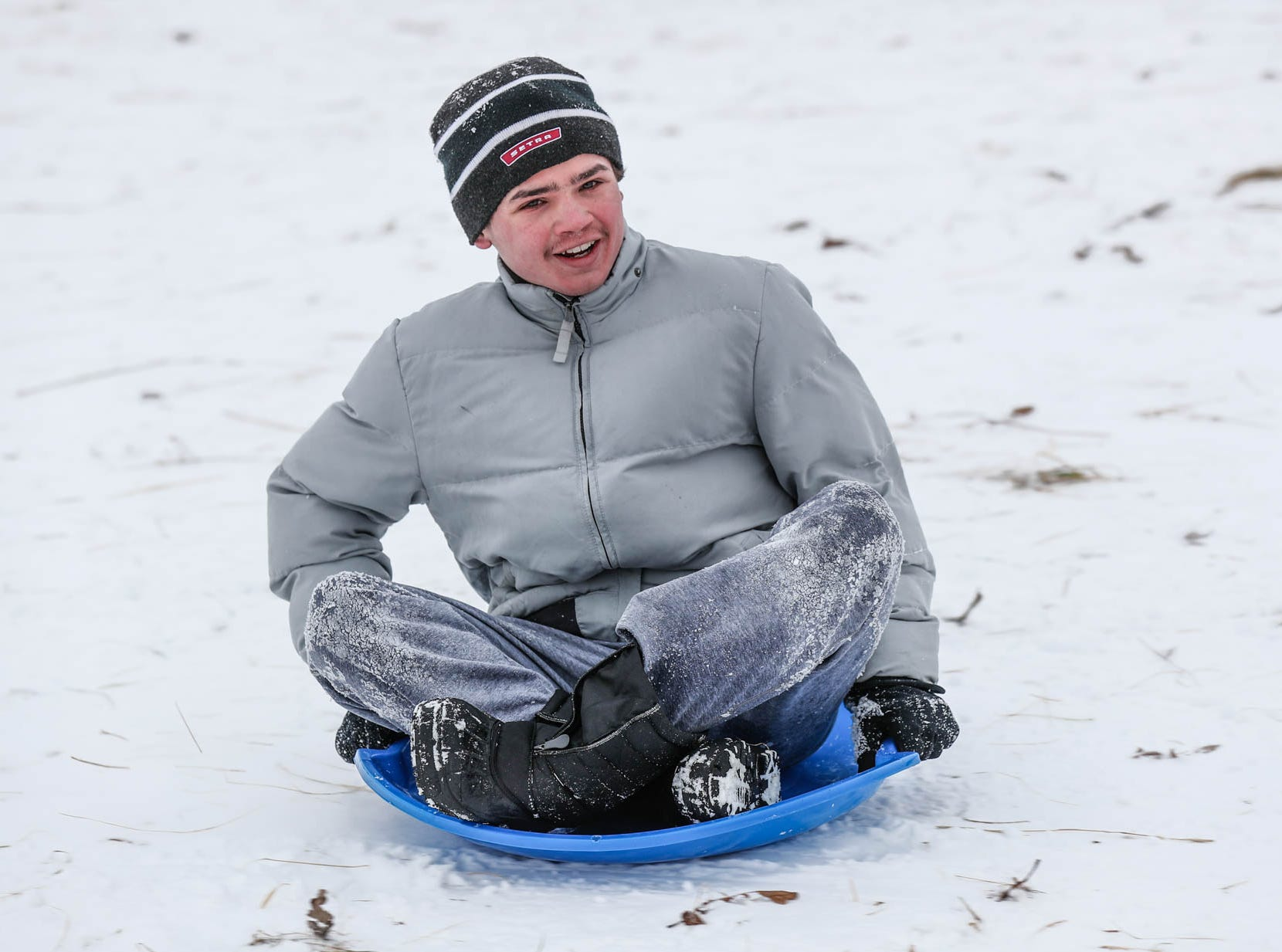 Isaac Cardwell zooms along on a saucer sled at West Park in Carmel Ind. on Sunday, Jan. 13, 2019.
