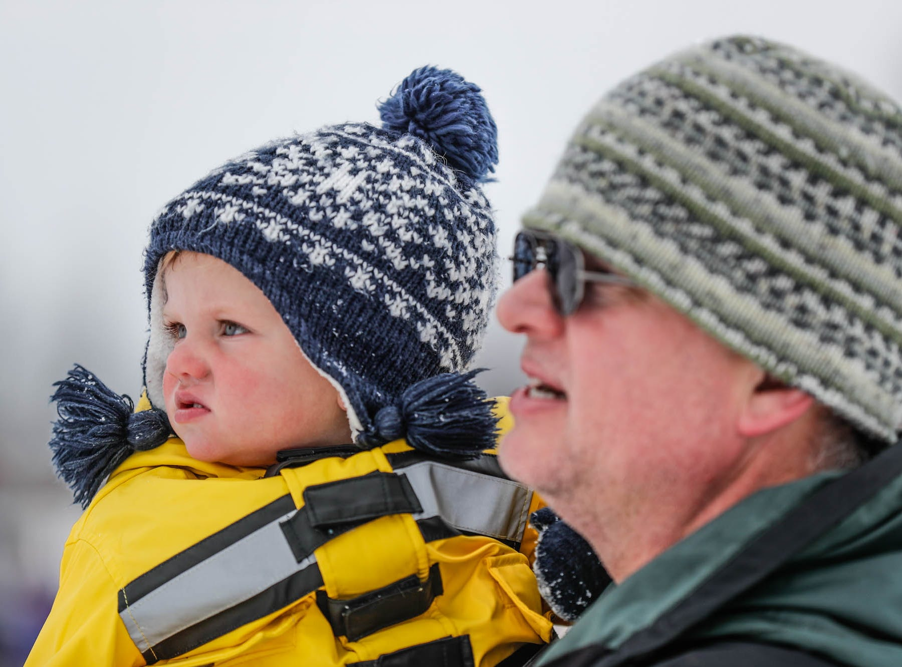 Chris Kendall holds his daughter Charlotte while watching  sledding at West Park in Carmel Ind. on Sunday, Jan. 13, 2019.