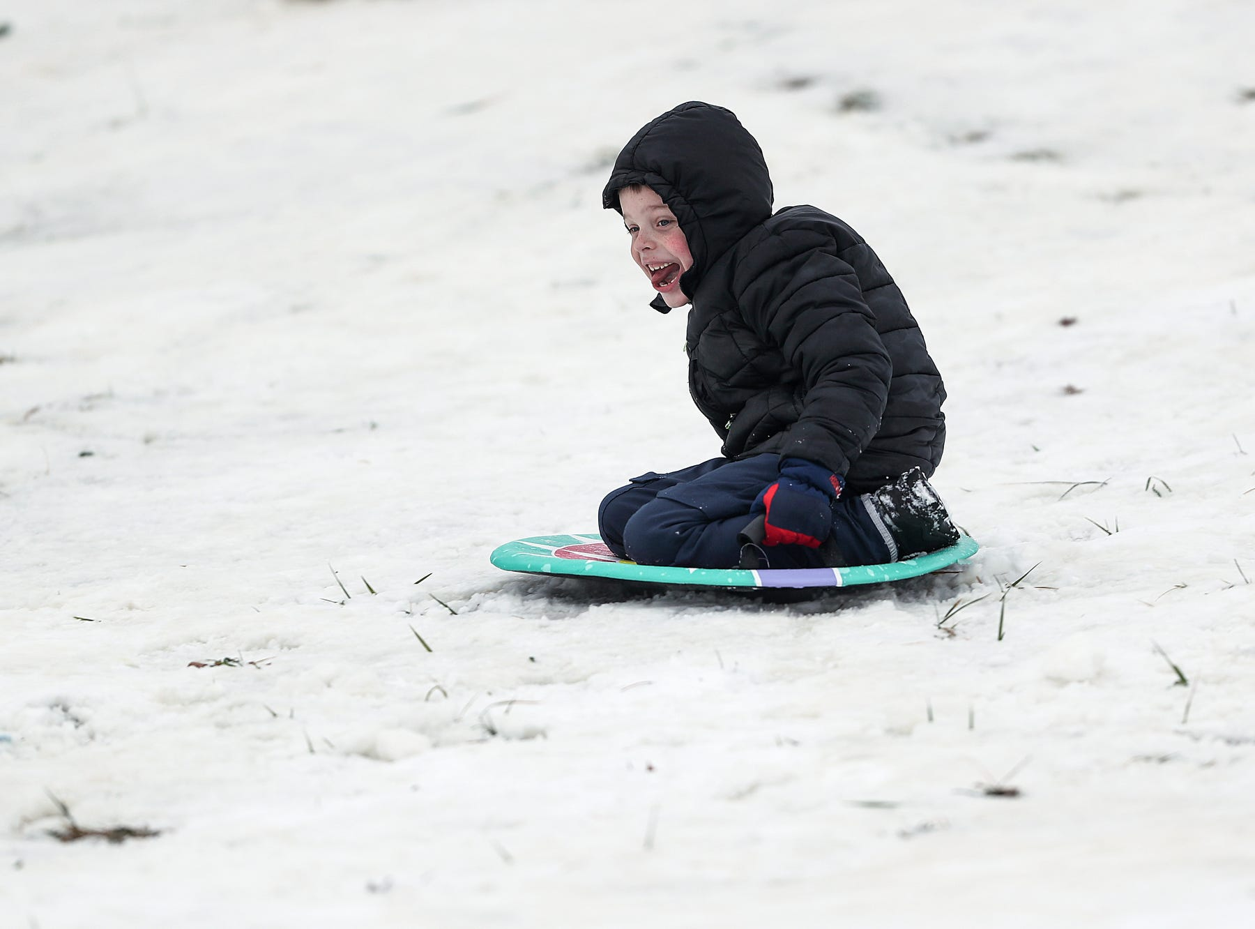 A child sleds down the hill at Ellenberger Park in Indianapolis, Sunday, Jan. 13, 2019.