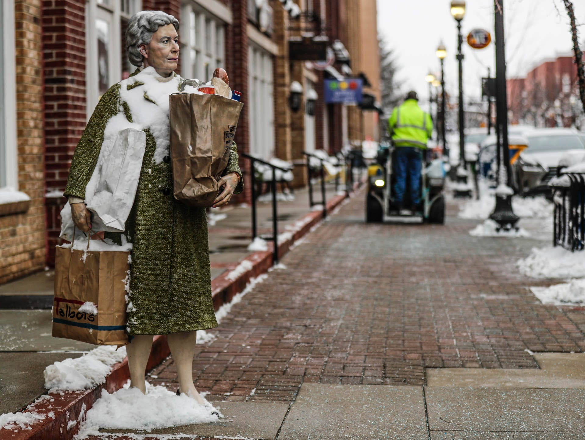 A sculpture by J. Seaward Johnson is dusted with snow as a unidentified man lays salt down on roads and sidewalks in downtown Carmel Ind. on Sunday, Jan. 13, 2019.
