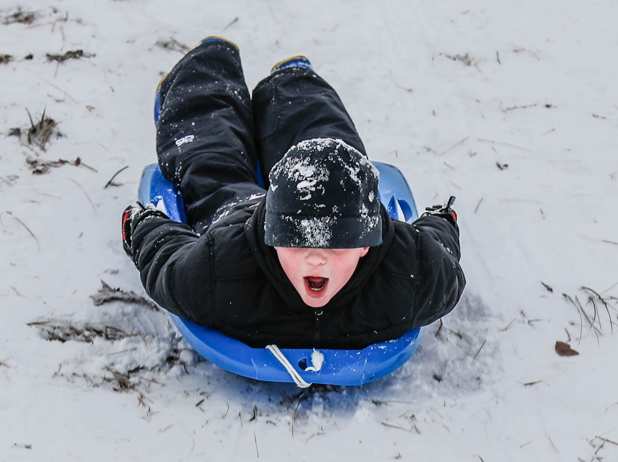 An unidentified child zooms down the sledding hill at West Park in Carmel Ind. on Sunday, Jan. 13, 2019.
