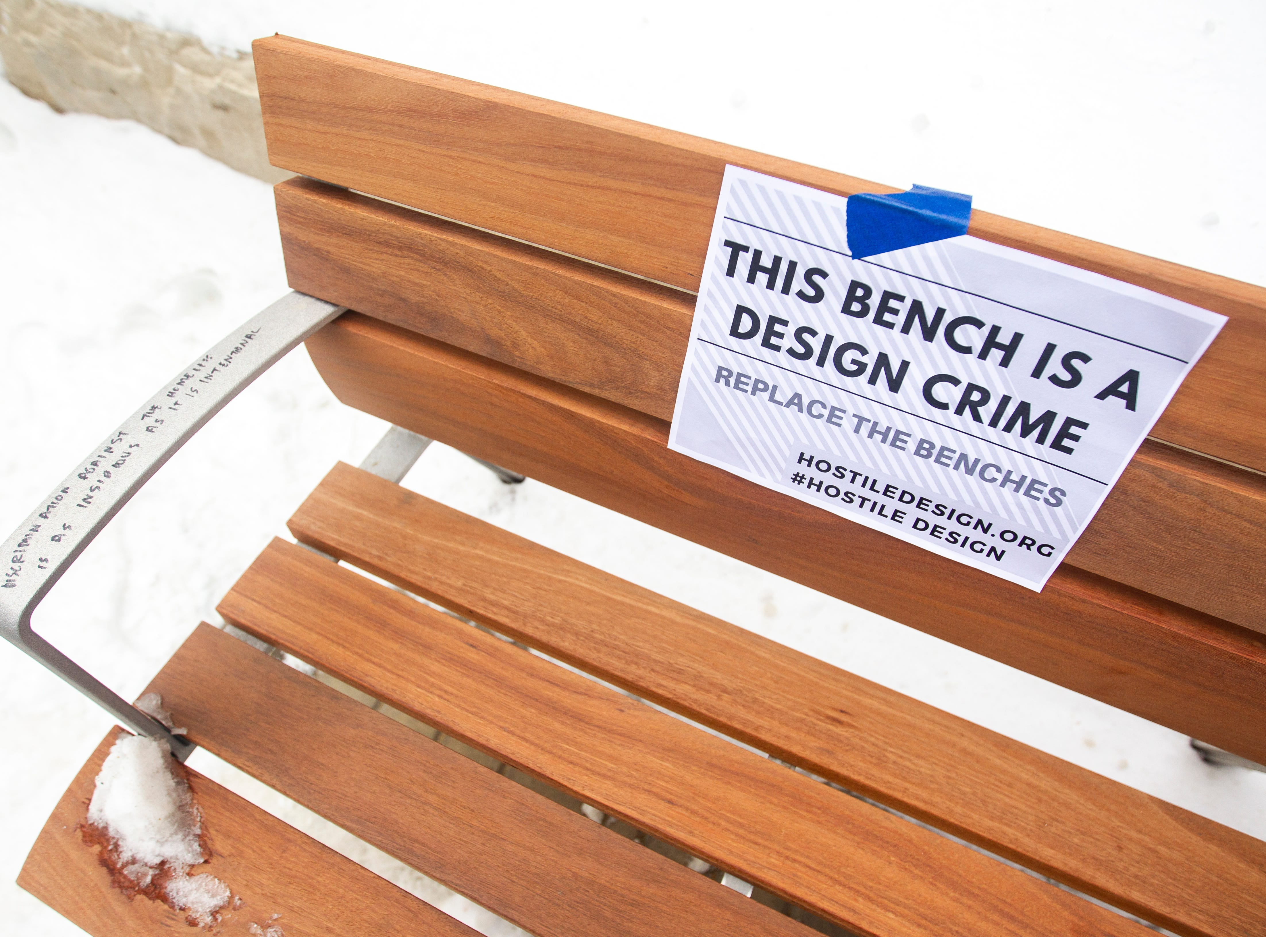 "A sign taped onto a new bench reads, ""This bench is a design crime,"" during the ""Sleep-In to Stop #HostileDesign"" on Monday, Jan. 14, 2019, along the pedestrian mall in downtown Iowa City, Iowa."