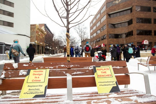 "Signs rest on new benches reading, ""Hostile design is a crime,"" and ""Replace the benches,"" during the ""Sleep-In to Stop #HostileDesign"" on Monday, Jan. 14, 2019, along the pedestrian mall in downtown Iowa City, Iowa."