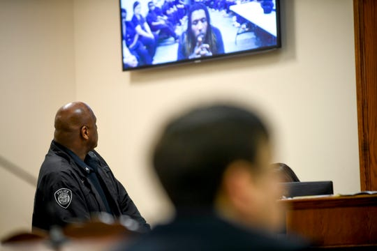 A Jackson Police officer watches the monitor displaying a livestream of the arraignment for Elijah Garrison in connection with the first fatal shooting in Jackson in 2019 at Jackson CIty Court in Jackson, Tenn., on Monday, Jan. 14, 2019.