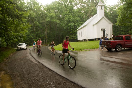 People ride past the Missionary Baptist Church in Cades Cove Wednesday, June 25, 2014. (J. MILES CARY/NEWS SENTINEL)