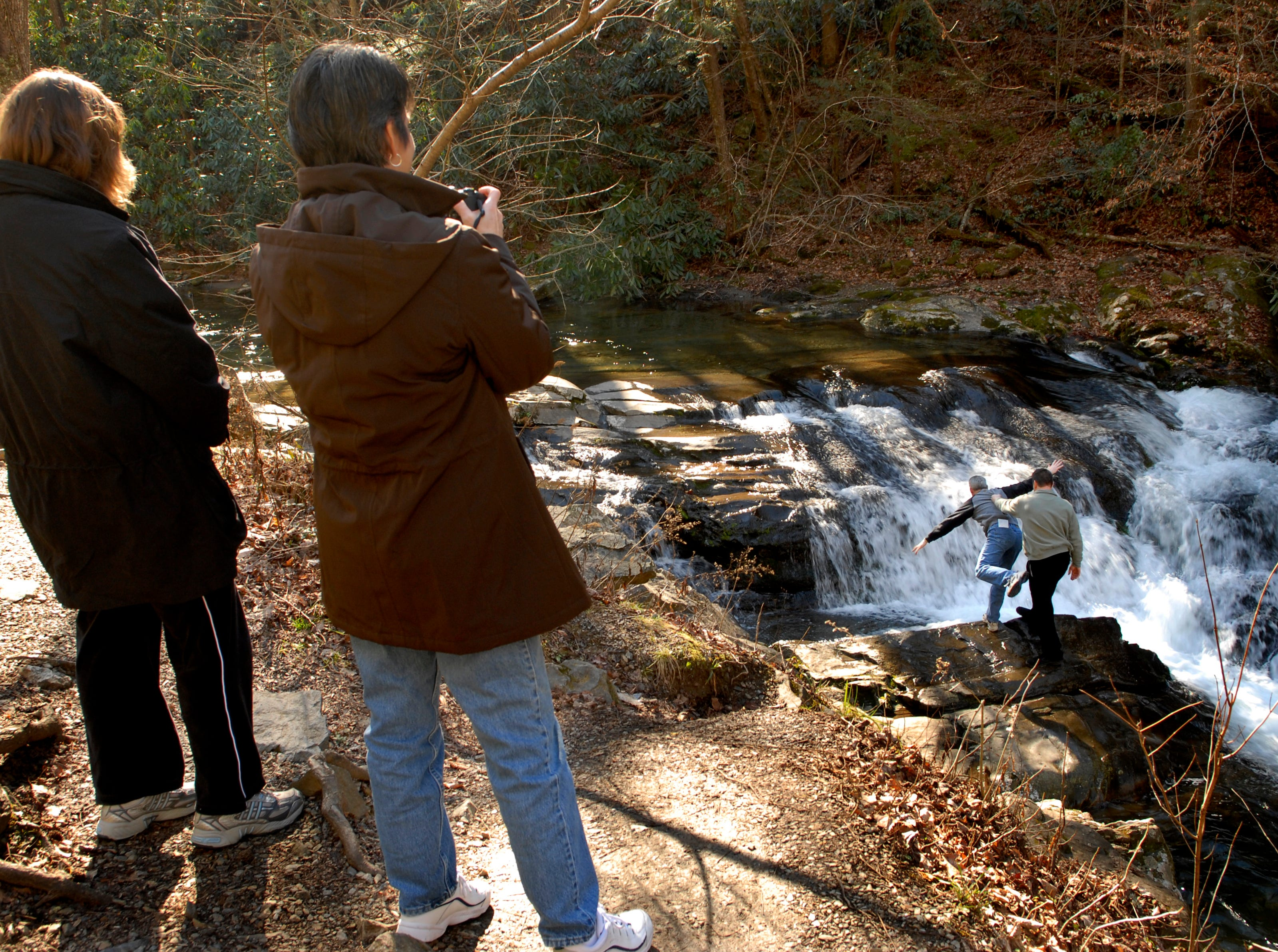 Johnna McDaniel, left, and Miram Williamson look on as their husbands, Mark Williamson and Robert McDaniel play on some rocks near the water along the Laurel Creek Road in the Great Smokey Mountains National Park, Friday. The two couples were visiting the park from Pinehurst, NC. January, 2007