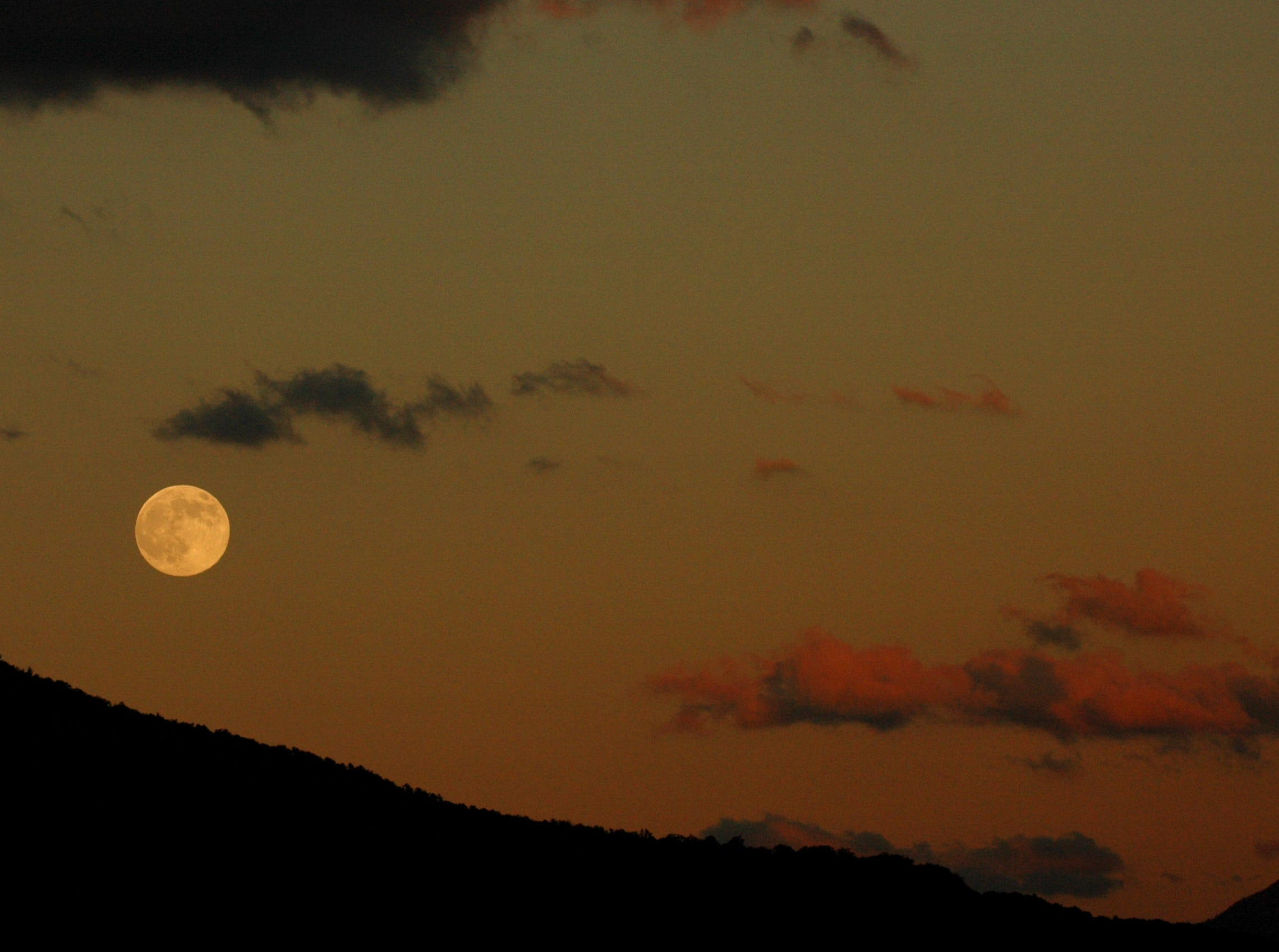 """A full moon, also known in October as the Full Hunter's Moon rises over Cades Cove on last week in the Great Smoky Mountains National Park. According to Stardate.org, a moon appearing larger on the horizon is an illusion and is not any further from Earth than when the moon is seen overhea in the night sky. """"When the Moon is nestled along the horizon we see it surrounded by a foreground of familiar Earth-bound objects. In comparison with these features, the bright disk of the full Moon appears quite large, and relative to our normal sense of the Moon's size, much bigger than we would expect."""" States the website."""