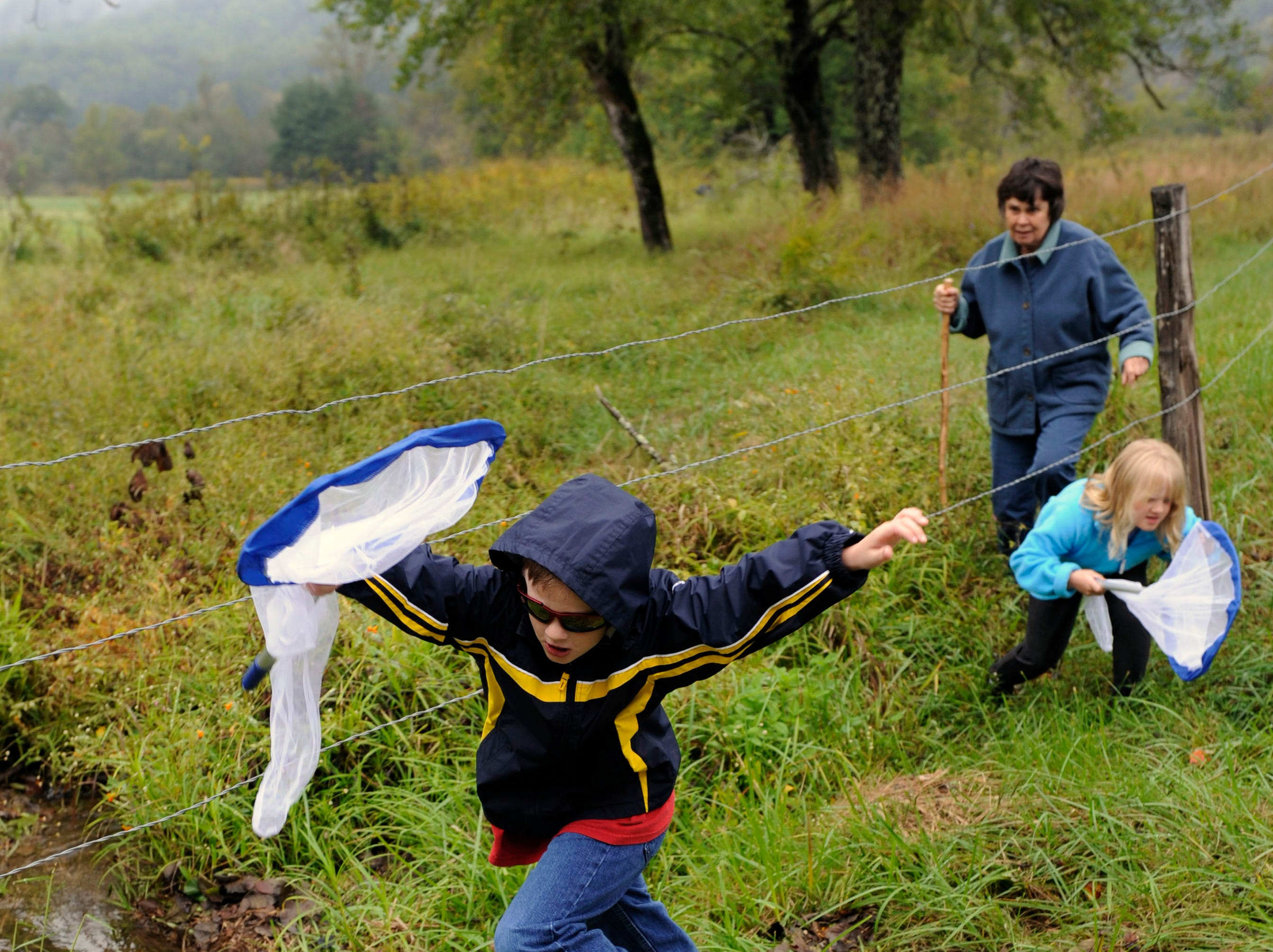 Danny Mick, 7, leaps over a stream of water while his twin sister Emma comes under the fence following him during a butterfly banding class  Tuesday, Sep. 28, 2010 in Cades Cove in the Smoky Mountains National Park. Another class member Ida Mae Patteson (cq) is top right.