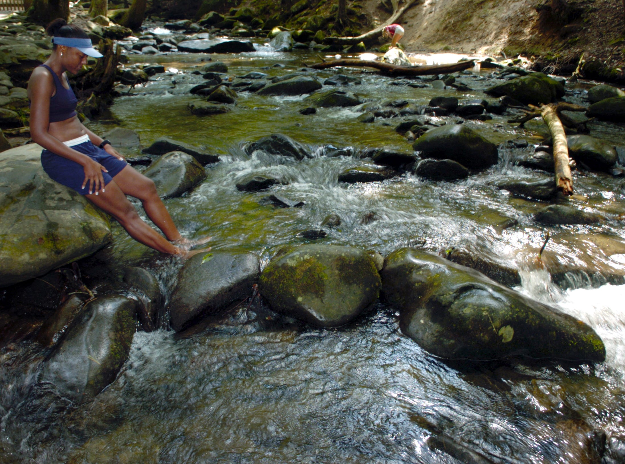 Kayla Montgomery cools her feet in a stream running out of the Great Smoky Mountain National Park following a 16 mile run in Cades Cove with a group of ladies to prepare for an all-woman Team in Training marathon.