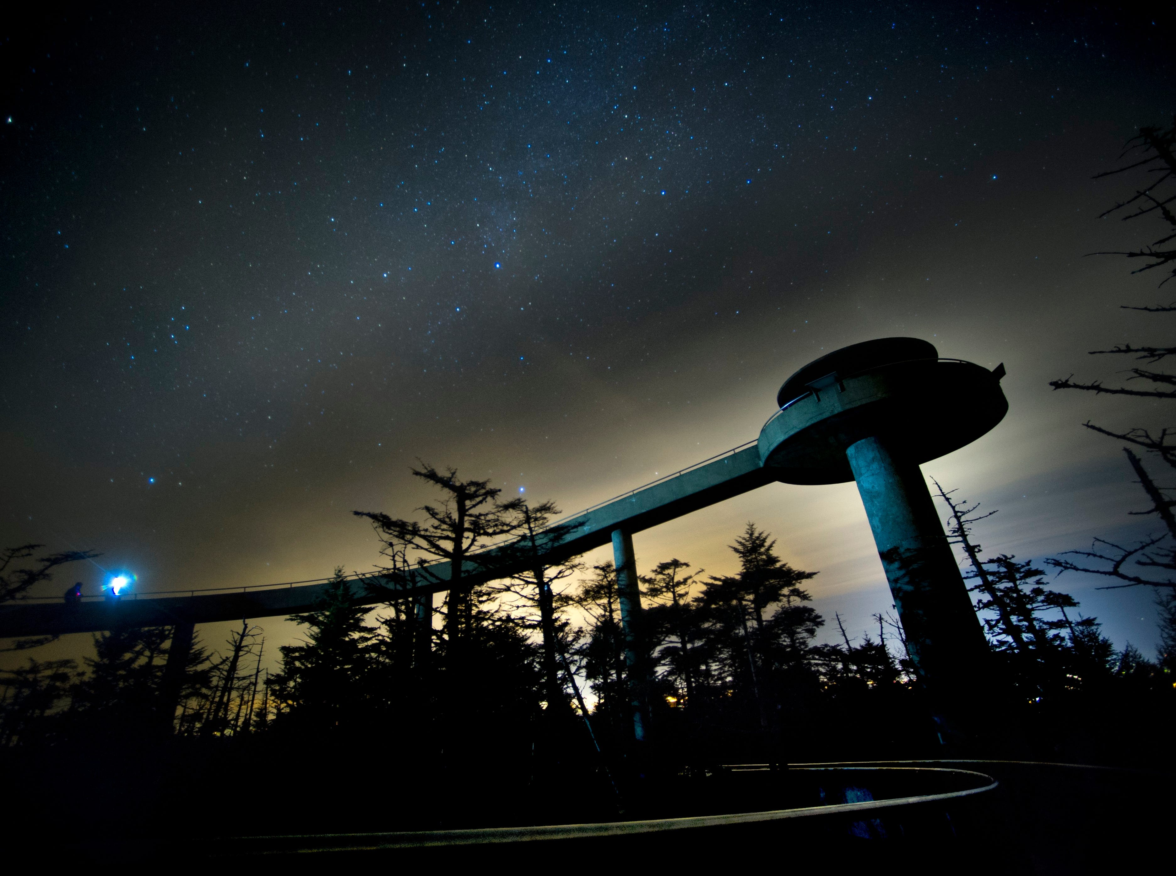 """Visitors Mike Henry of Ann Arbor, Mich. and Matt Hutton of San Luis Obispo, Calif. round the walkway to the Clingmans Dome observation tower beneath starry autumn skies on Saturday, Nov. 30, 2013 in the Great Smoky Mountains National Park. The two made their nighttime stop at Clingmans while on a trip to visit all the """"high points"""" in the continental U.S. At 6,643 feet high, Clingmans Dome is the third highest mountain east of the Mississippi, and the highest point in Tennessee. The site remains open year-round, but the seven-mile paved road leading to Clingmans closes during winter, and will reopen Apr. 1. (ADAM LAU/NEWS SENTINEL)"""