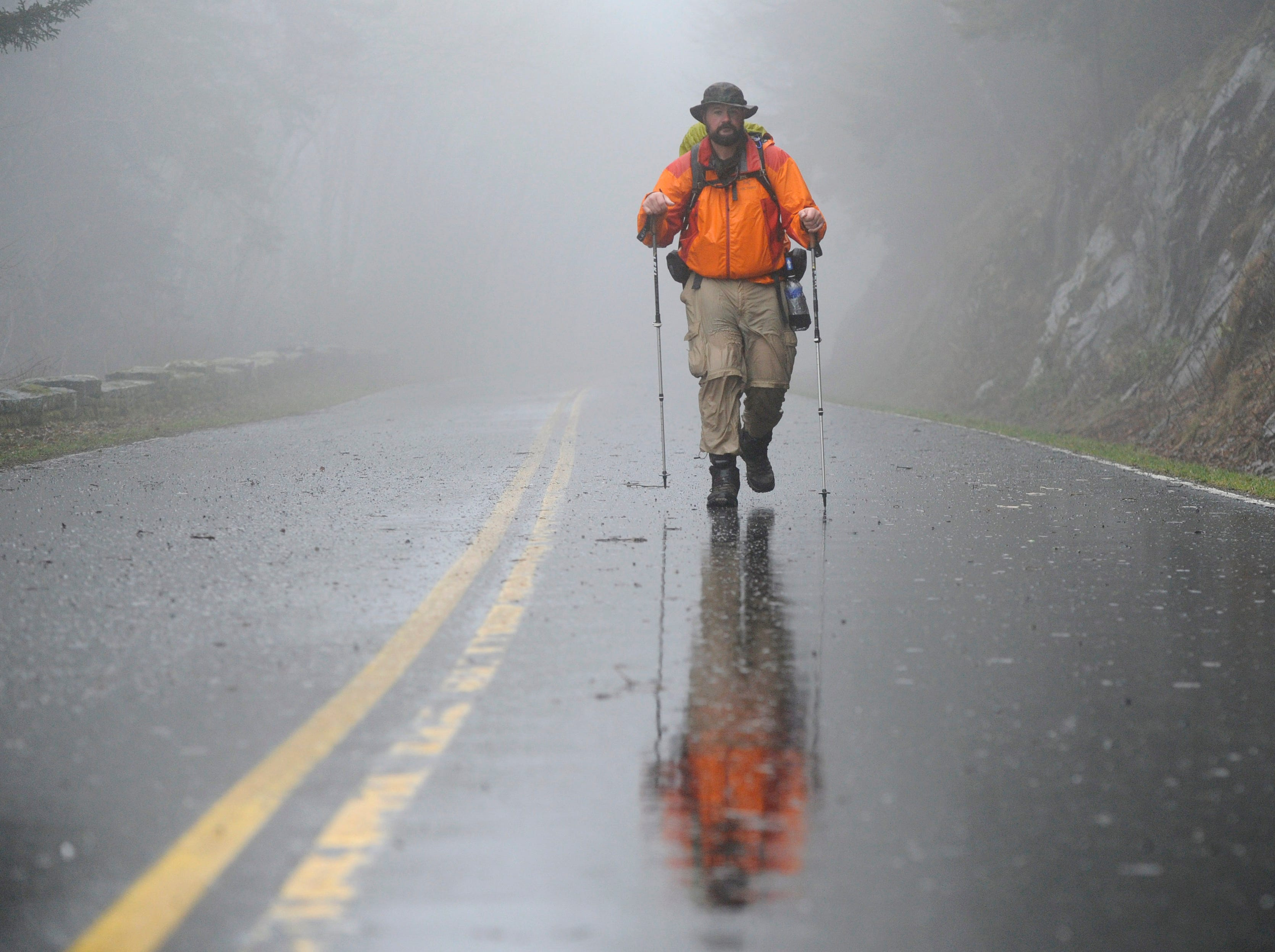 Jeff Fowler hikes down Clingmans Dome Access Road towards Newfound Gap while detouring from the Appalachian Trail due to heavy rains on Thursday, March 19, 2015. Fowler and friend, Don Nguyen, both ex-Marines, are thru-hiking the AT to raise money for Higher Ground, a non-profit rehabilitation program for military veterans. (ADAM LAU/NEWS SENTINEL)