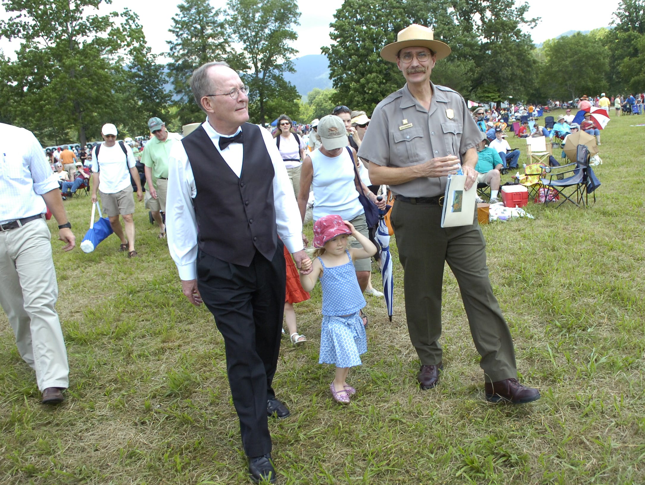 Senator Lamar Alexander walks toward the concert stage with his granddaughter, three year-old Taylor Irwin, and Great Smoky Mountain National Park Superintendent Dale Ditmanson during the 75th Anniversary Celebration Concert in Cades Cove featuring the Knoxville Symphony Orchestra and Senator Alexander. The event drew and estimated 5,000 concertgoers to the cove on Saturday afternoon.