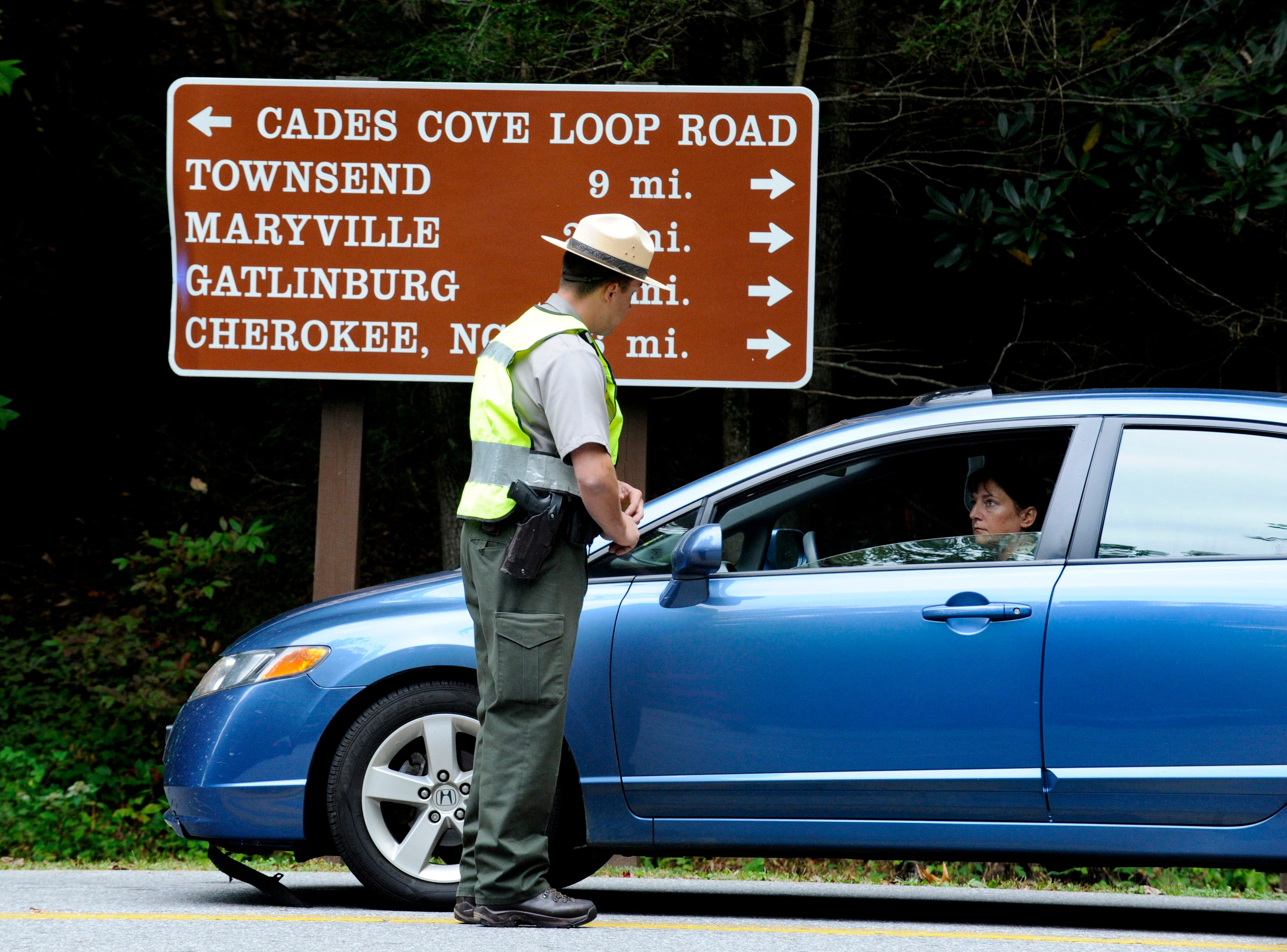 National Park Service Ranger Phil Basak explains to visitors to Cades Cove in the Great Smoky Mountain National Park Tuesday, Oct. 1, 2013 that the loop road will be closed as long as the government is shut down. (MICHAEL PATRICK/NEWS SENTINEL)