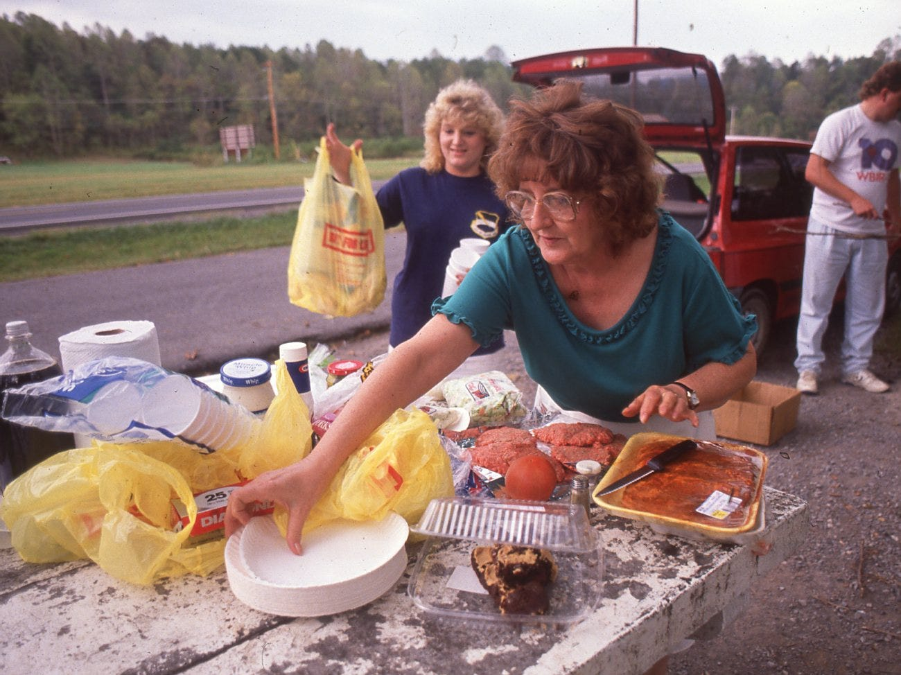 Helen Lunsford prepares to cook hamburgers for her family (Tracy Ingle, left and Eddie Lunsford) at a rest area. Lunsford had travels from Harriman for a picnic in Cades Cove but found the park closed, October, 1990.