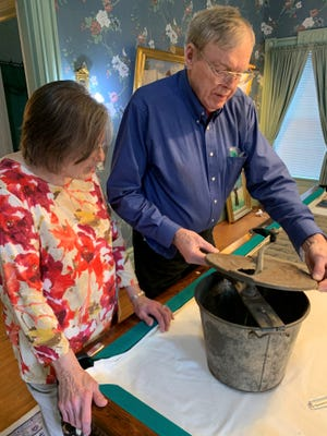 """Bob and Ellie Haan, of the Haan Mansion Museum of Indiana Art, open a tin bread kneader, which was displayed and sold as a state-of-the-art appliance at the 1904 St. Louis World's Fair. The museum opens an exhibition titled """"St. Louis World's Fair: Celebrating 115 Years"""" on Jan. 26."""