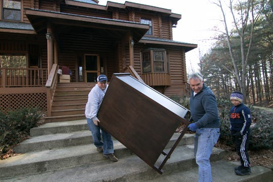 Kenny Lindsay, owner and auctioneer of Kenny Lindsay's American Eagle Auction and Appraisal Co., at left, and auction manager Bob Goetz help load a dresser to the car of high bidder Stacy Luoma of Redford Monday, Jan. 14, 2019 after the close of the Melissa Gilbert and Timothy Busfield estate auction. Giving guidance to the two is Lindsay's 9 1/2-year old son Carson, who tells them when a step is coming.