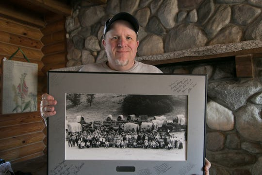 """Kenny Lindsay, owner of American Eagle Auction and Appraisal Co., holds an original cast and crew photo from the production of the television show, """"Little House on the Prairie,"""" Monday, Jan. 14, 2019, a photo which sold for $1200 to the Laura Ingalls Wilder Museum from the estate of Melissa Gilbert and Timothy Busfield."""