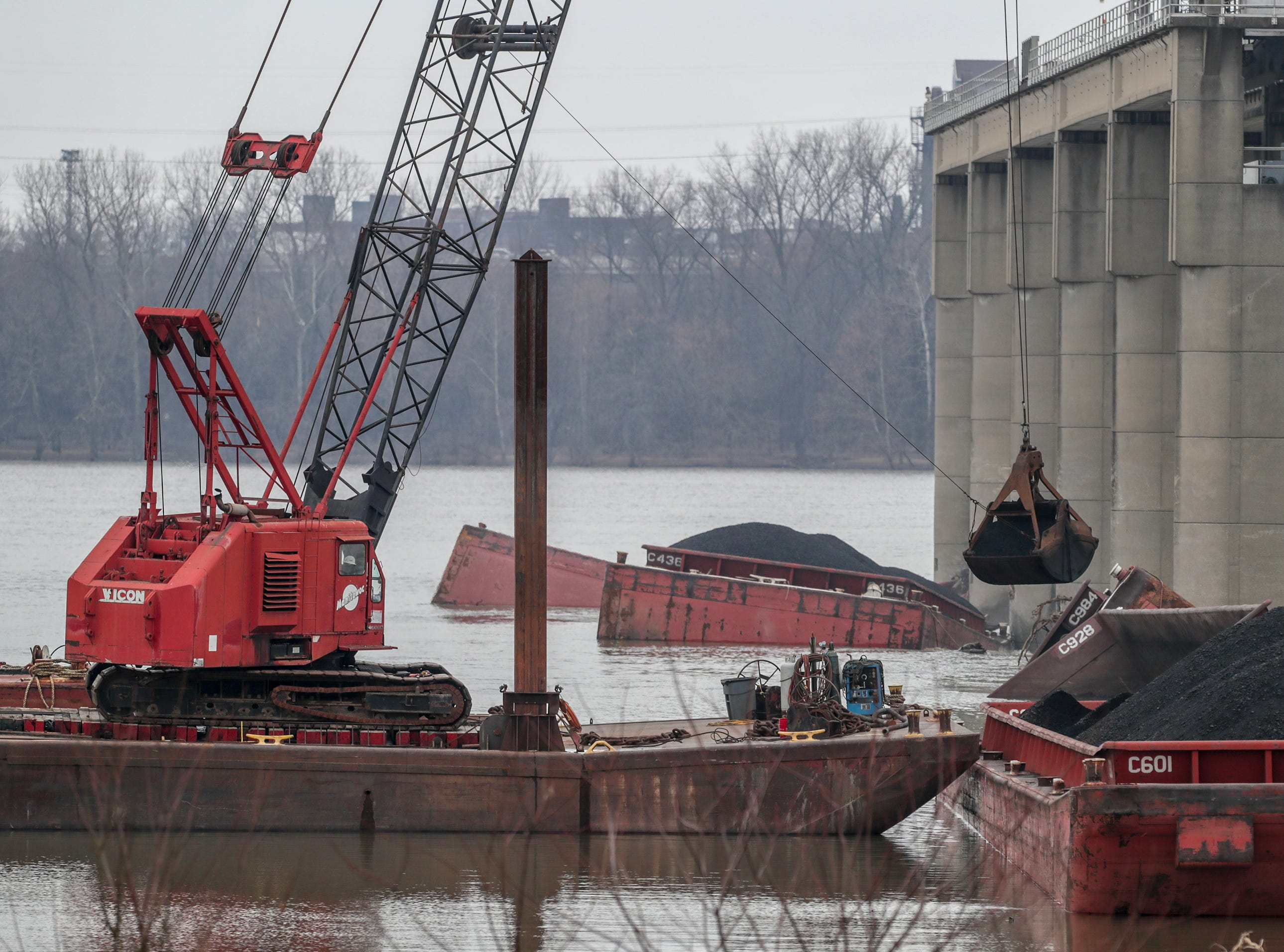 Crews are making progress clearing coal-laden barges from the dam and spillway on the Ohio River. Two barges have been removed and work has begun on a third.