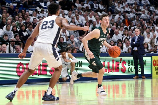 Michigan State's Foster Loyer is defended by Penn State's Josh Reaves during the second half Sunday in State College, Pa. Loyer finished with seven points in 11 minutes, in what Tom Izzo called one of Loyer's better games of the season.