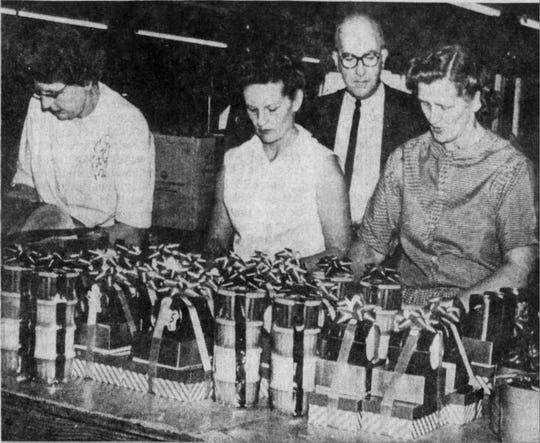 John Figi, president and founder of Figi's Inc., watches as Mrs. Wallace Callias, Mrs. Phyllis Coaty and Mrs. Leonard Bauer wrap gifts during the holiday season in this Nov. 13, 1964, photo.