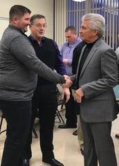 Former board member Loren Blackstone (center) and superintendent Mike Ziegelhofer (right) congratulate new Lexington head football coach Tim Scheid.