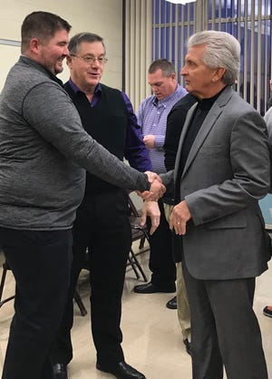 Lexington Superintendent Mike Ziegelhofer, right, congratulates football coach Tim Scheid in a file photo. The longtime superintendent announced his intent to retire effective Aug. 1 at Wednesday's board of education meeting.
