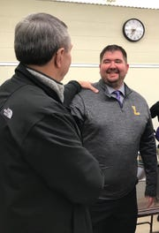 Tim Scheid, the new Lexington football coach, receives congratulations from board member Dave Roberts on Monday morning.