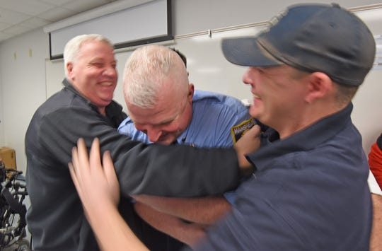 Newly promoted to lieutenant, Matthew Shafley is congratulated with a hug from his firefighting peers during a ceremony on Monday morning at the Main Street Fire Station.