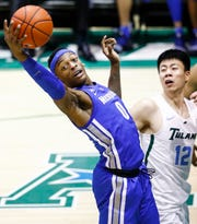 Memphis forward Kyvon Davenport (left) grabs a rebound in front Kevin Zhang (right) of Tulane defender during action in New Orleans, Sunday, January 13, 2019.