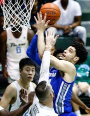 Memphis forward Isaiah Maurice (right) drives to the basket against the Tulane defense during action in New Orleans, Sunday, January 13, 2019.