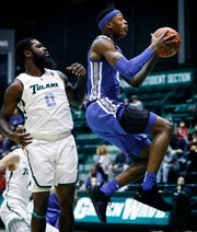 Memphis froward Kyvon Davenport (right) drives for a layup by Tulane defender Jordan Cornish (left) during action in New Orleans, Sunday, January 13, 2019.