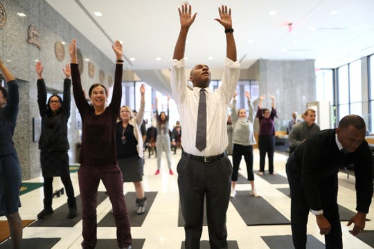 Shelby County Mayor Lee Harris, center, joins fellow commissioners and staff as they take part in a mini boot camp fitness training session downtown with instructor and former University of Memphis basketball player Will Coleman Monday, Jan. 14, 2019.
