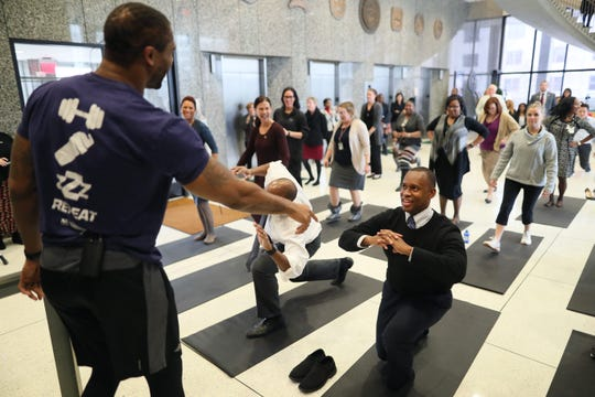 Will Coleman, fitness instructor and former University of Memphis basketball player, points out the solid form of Shelby County Commissioner Van Turner's lunges as county workers participate in a mini boot camp training session downtown Monday, Jan. 14, 2019.